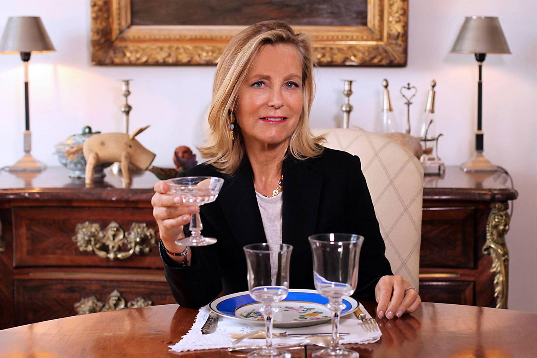 Femme à table avec un verre à la main